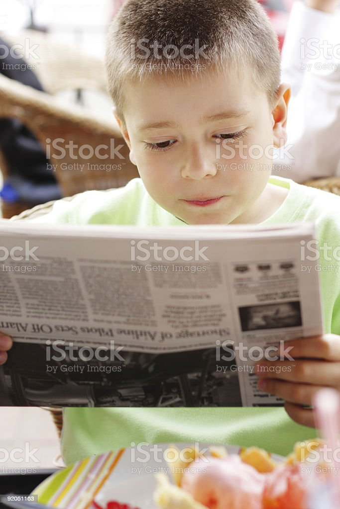 Young boy intently reading the newspaper stock photo