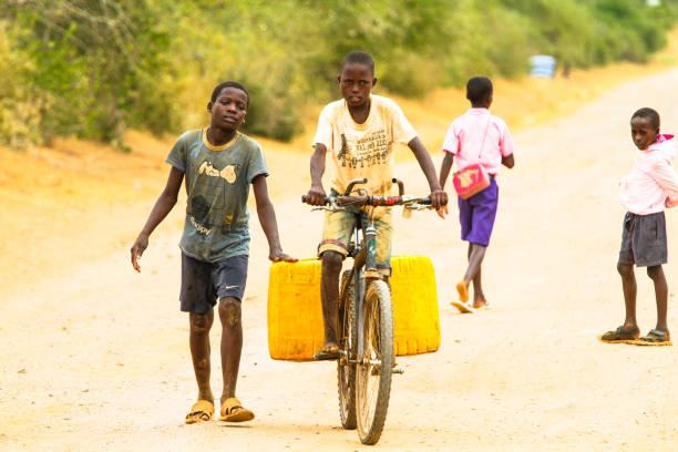 ein kleiner junge ist wasser vom nächstgelegenen hydranten zu sich nach hause tragen. - fahrradträger stock-fotos und bilder