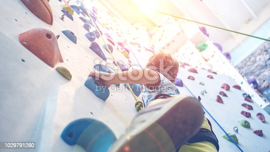 istock young boy is climbing an indoor climbing wall 1029791260