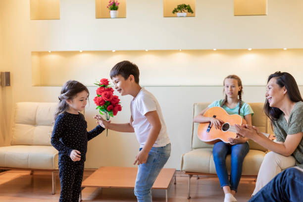 Young Boy is Giving a Bouquet of Red Flowers to his Cute Sister. Cheerful and Happy Family is Enjoying in Birthday Party at Home while Young Girl is Playing an Acoustic Guitar. group of friends giving gifts to the birthday girl stock pictures, royalty-free photos & images