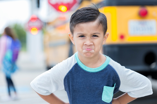 Mixed race elementary school boy makes a face before boarding a school bus. He is not ready to go back to school. He is looking at the camera. His hands are on his hips.