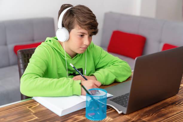 어린 소년이 노트북 앞에서 공부하고 있습니다. e 학습, 온라인 집에서 공부. - 멀리 떨어진 뉴스 사진 이미지