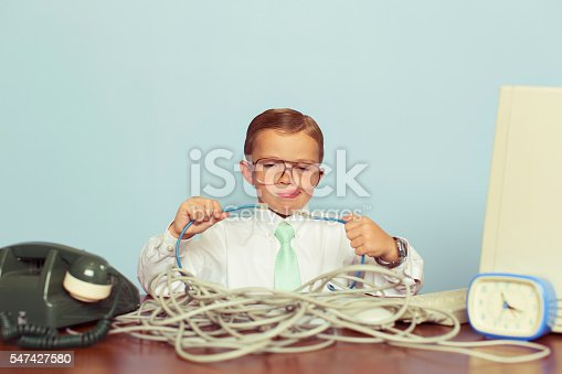 A young IT professional working with a large pile of tangled internet cables on his desk. He is dressed in a white shirt, tie and glasses while trying to reconnect his broken network. Retro styling. This IT technician can solve any network problem.