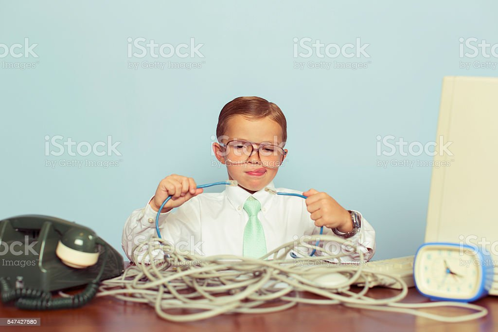 Young Boy IT Professional Smiles at Computer with Wire - foto de stock