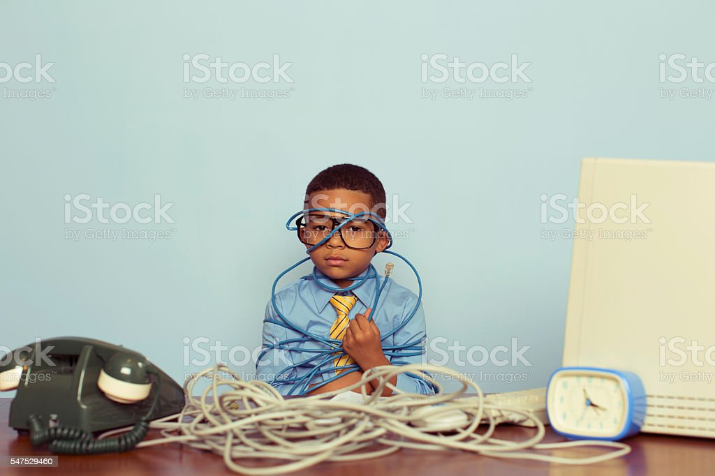 Young Boy IT Professional Smiles at Computer with Wire stock photo