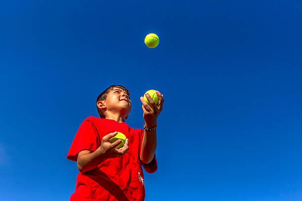 Young boy juggles balls. stock photo