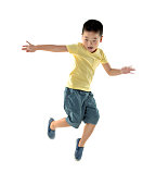 Young boy jumping against white background.