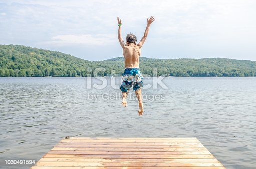 Young boy jumping in a lake from the pier during summer day
