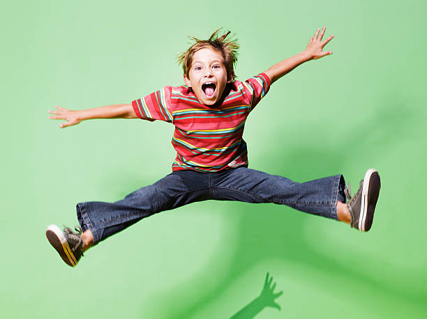 Young boy jumping in mid-air  mid air stock pictures, royalty-free photos & images