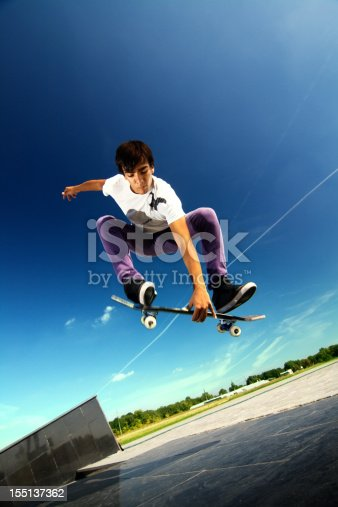 istock Young boy jumping in the air on a skateboard 155137362