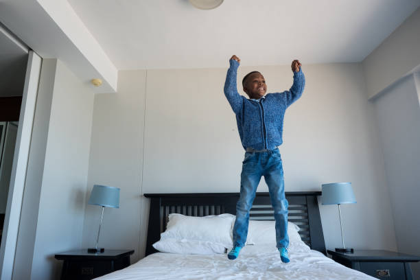 Young boy jumping on the bed stock photo