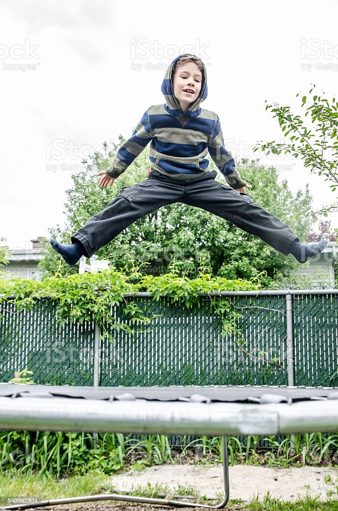 Young boy jumping on trampoline in backyard stock photo