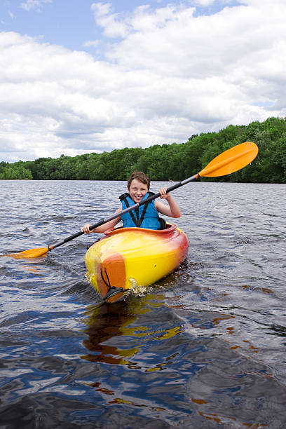 A young boy kayaking in a big lake stock photo