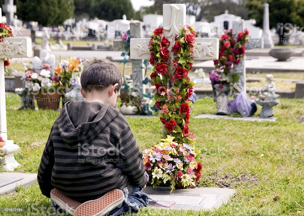 Young boy kneeling at a grave grieving royalty-free stock photo