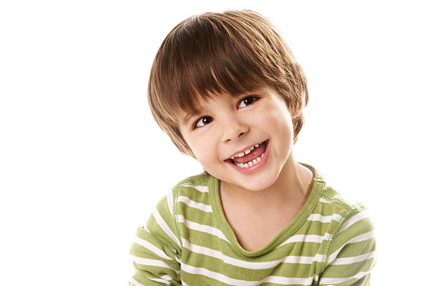 Young boy laughing in green top against white background stock photo