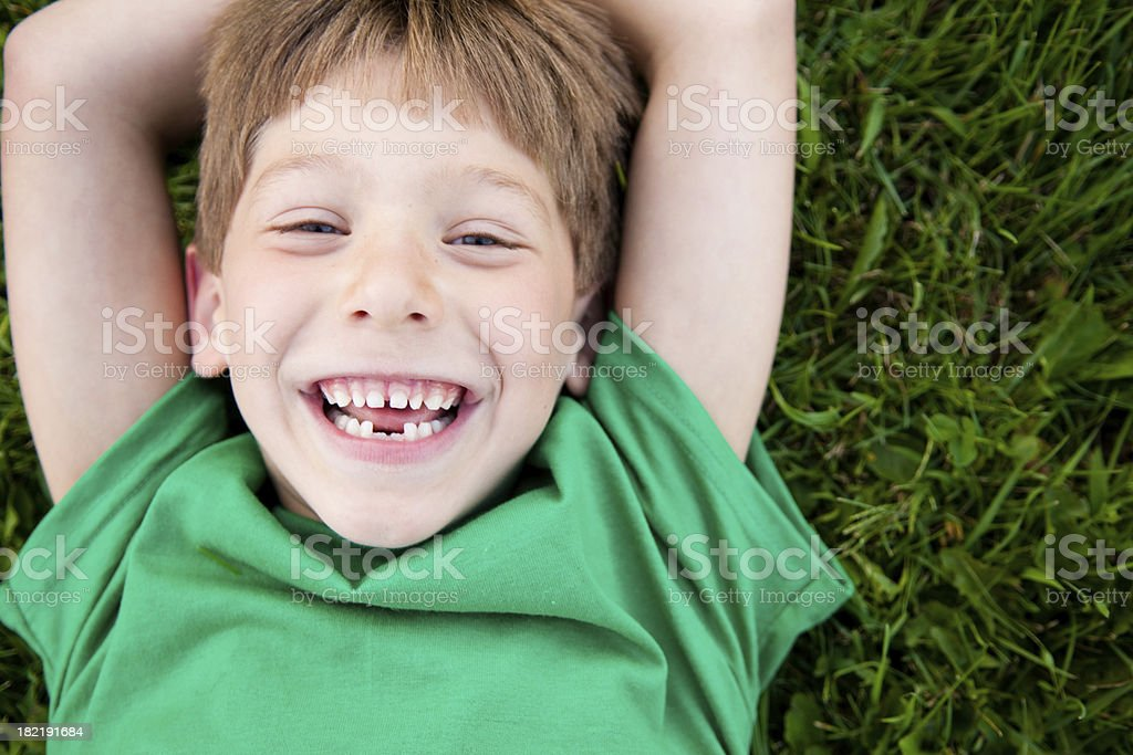 Young Boy Laughing while Lying in the Grass stock photo