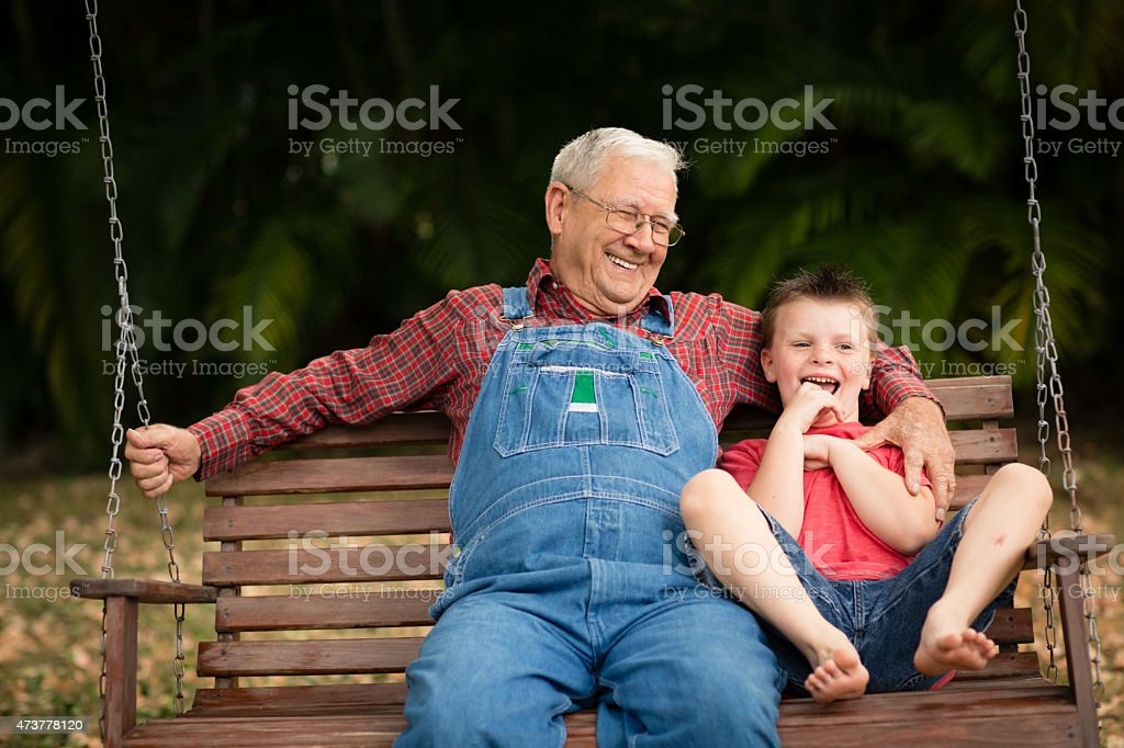 Young Boy Laughing With His Great Grandfather on Swing stock photo
