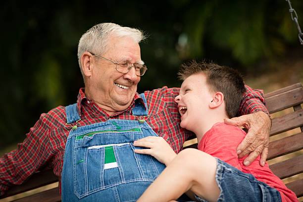 Young Boy Laughing With His Great Grandfather Color image of a little boy laughing with his grandpa as they sit on a porch swing outdoors. bib overalls boy stock pictures, royalty-free photos & images
