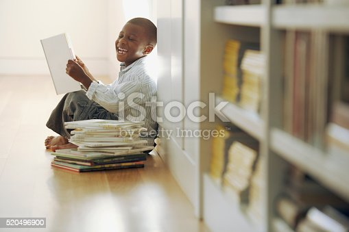 istock Young boy laughs at a storybook 520496900