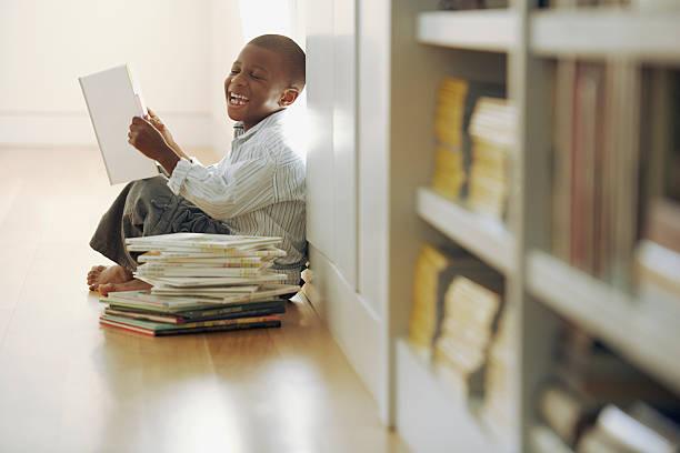 young boy laughs at a storybook - humor bücher stock-fotos und bilder