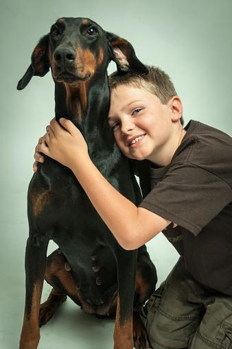 Young boy leaning against doberman dog