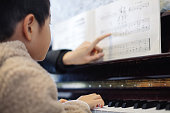 Young boy learning to play piano