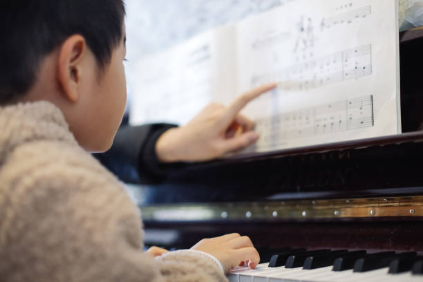 Young boy learning to play piano stock photo