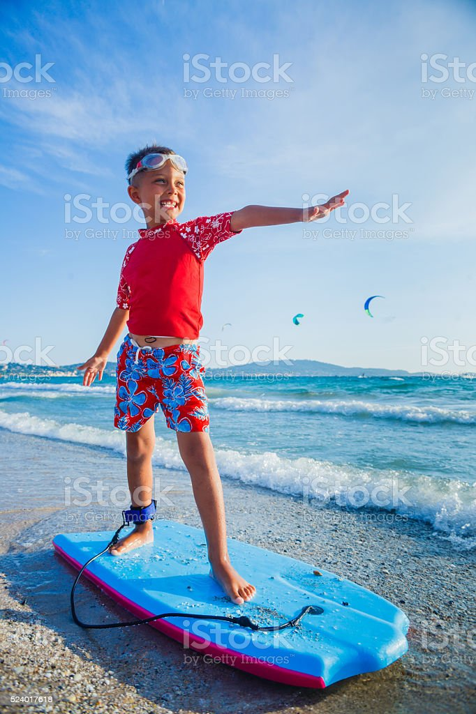 Young boy learning to surf stock photo