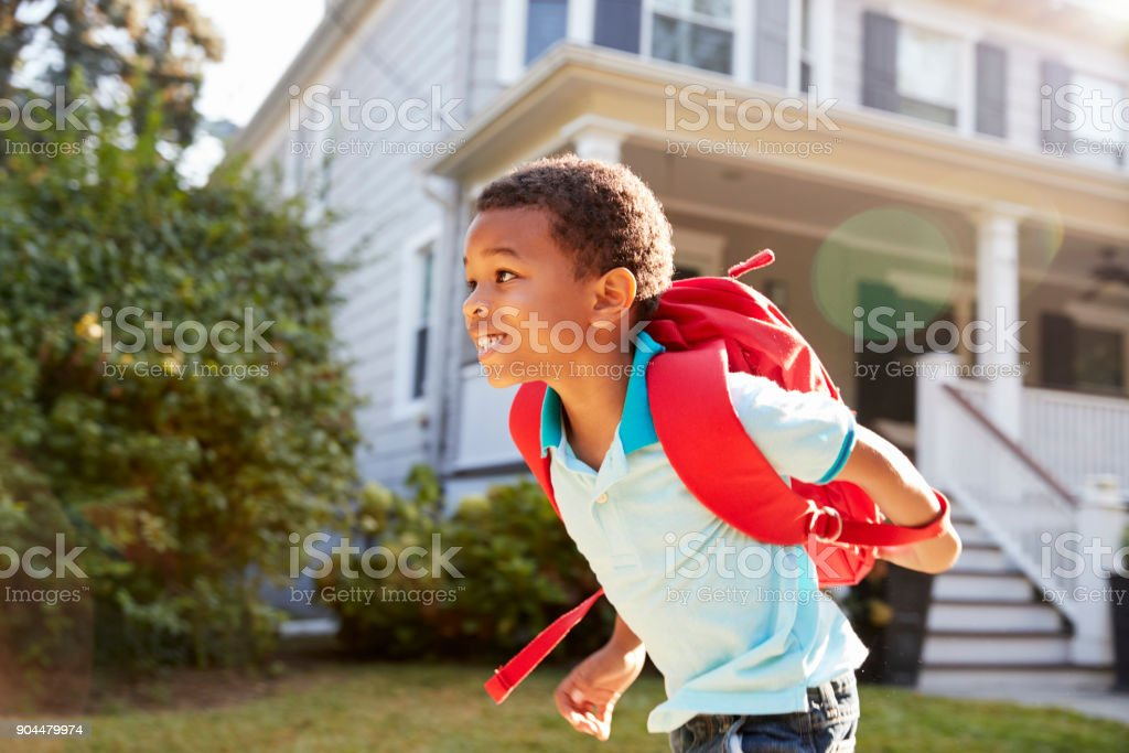 Young Boy Leaving House To Walk To School stock photo