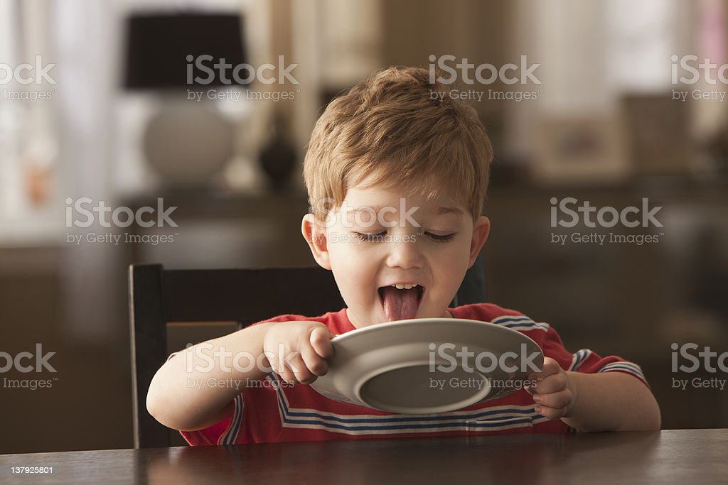 Young boy licking plate stock photo