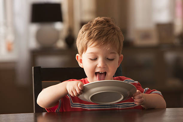 Young boy licking plate  licking stock pictures, royalty-free photos & images