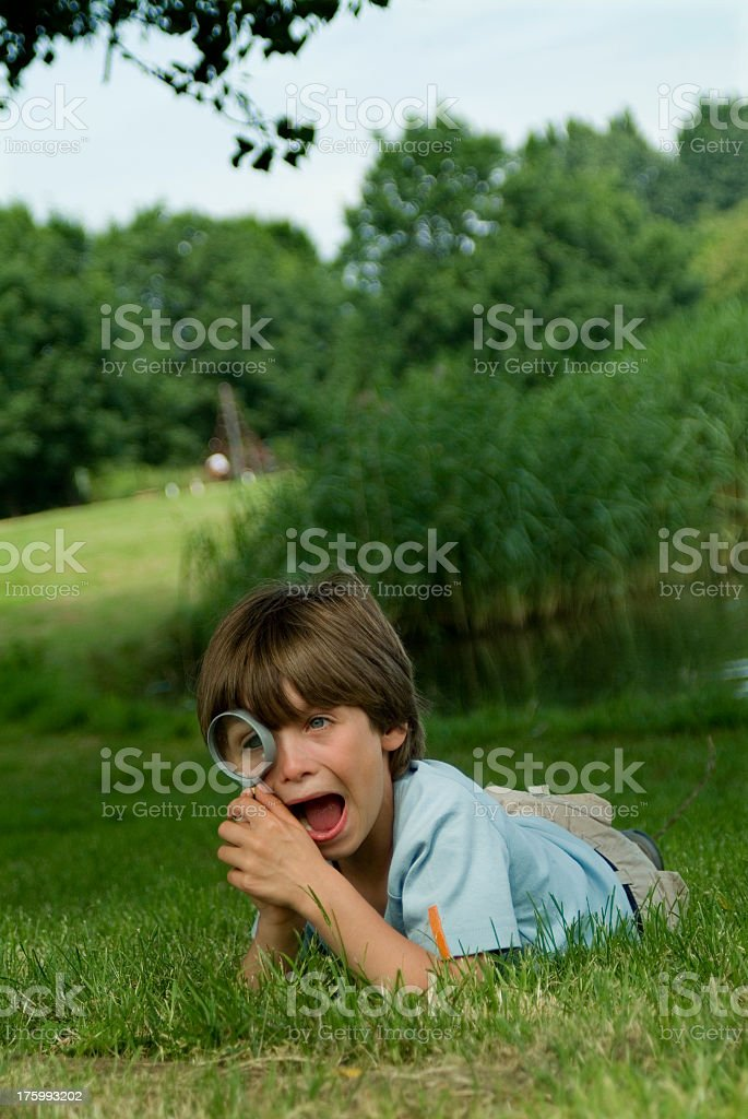 young boy lie in grass  oudoors with magnifying-glass stock photo