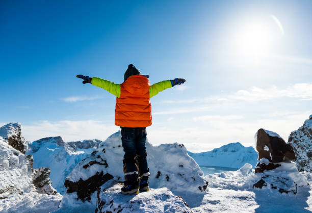 Young boy lifts his arms on the top of snow mountains stock photo