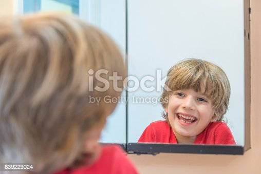 istock Young boy looking at himself in mirror 639229024