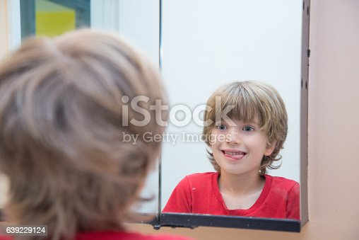 istock Young boy looking at himself in mirror 639229124