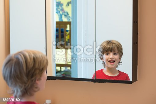 istock Young boy looking at himself in mirror 639229180
