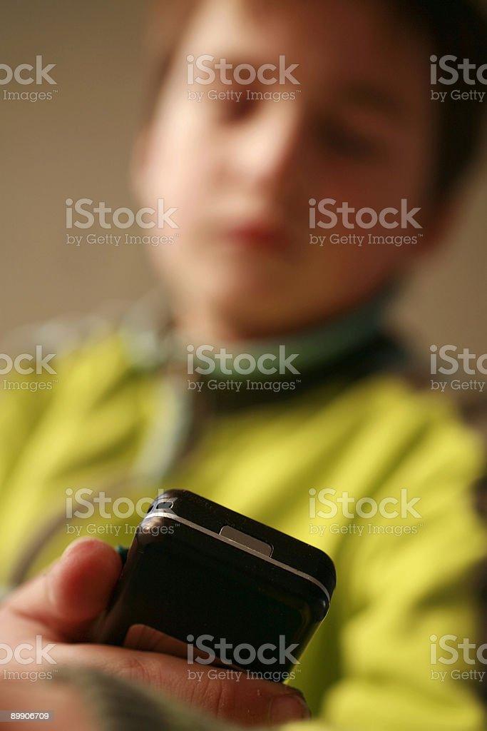 young boy looking at su teléfono móvil foto de stock libre de derechos