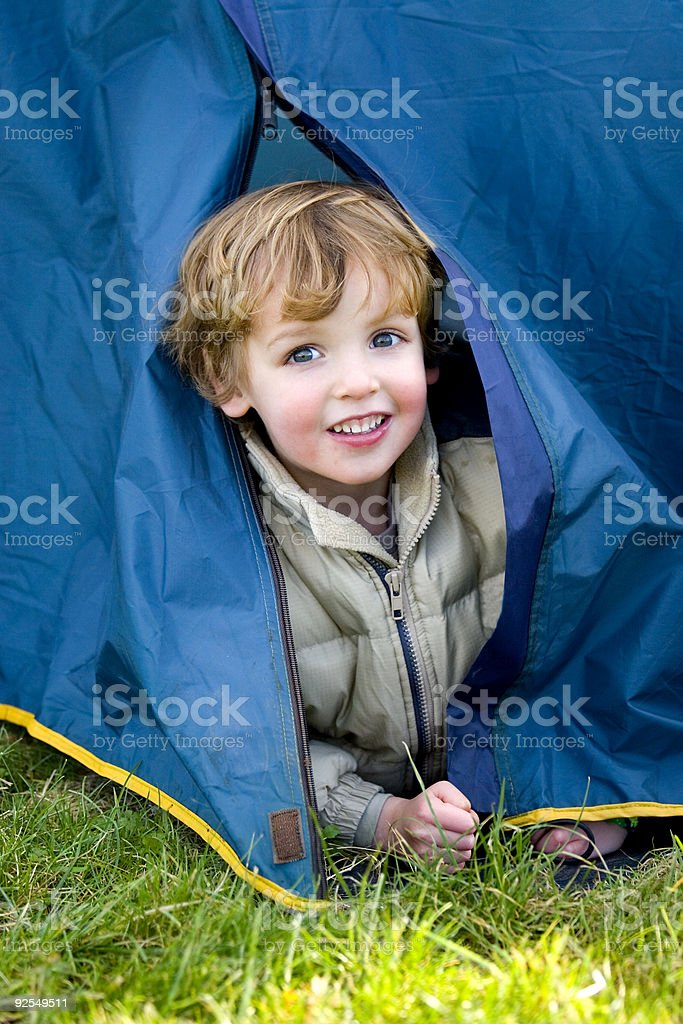 Young Boy Looking Out of His Tent First Time Camping stock photo
