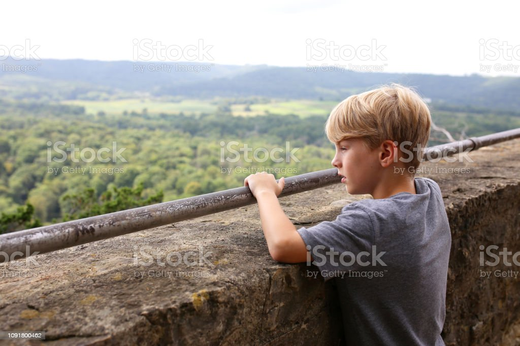 Young Boy Looking Out over Ledge of Tourist Scenic Cliff Viewing Deck stock photo