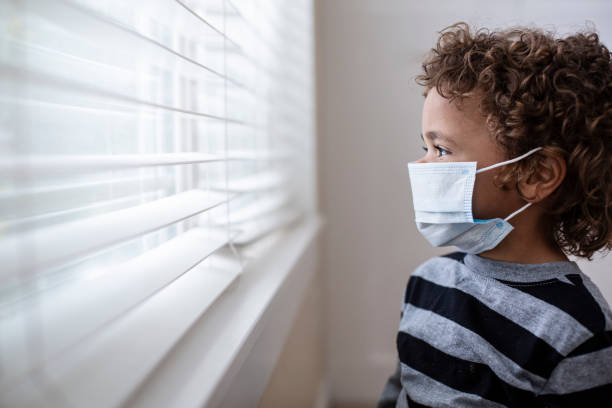 A young boy looking out the window wearing a protective facemark while seeking protection from COVID-19 stock photo