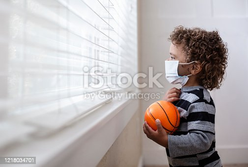 A young boy looking out the window wearing a protective facemark while seeking protection from COVID-19, or the novel coronavirus, by sheltering in place in his home.