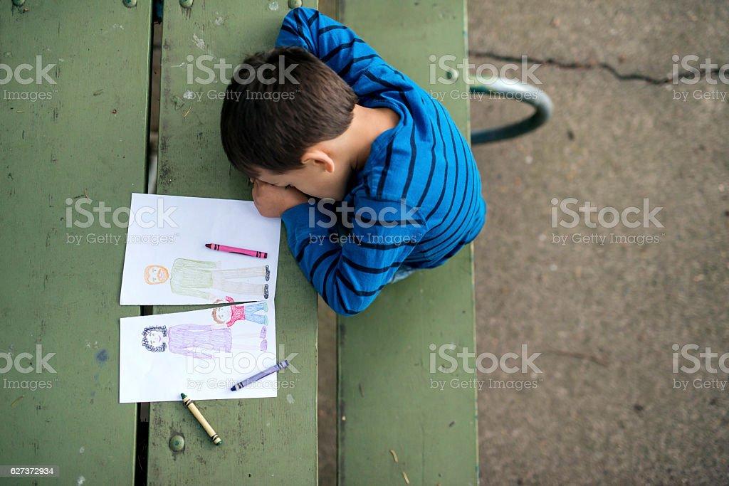 Young boy looking sad at drawing of a broken family stock photo