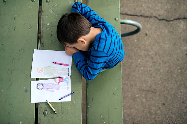 young boy looking sad at drawing of a broken family - scheidung stock-fotos und bilder