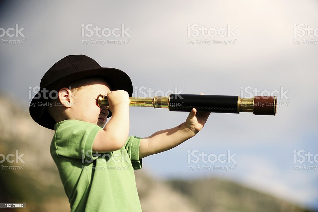 Young boy looking through a telescope stock photo