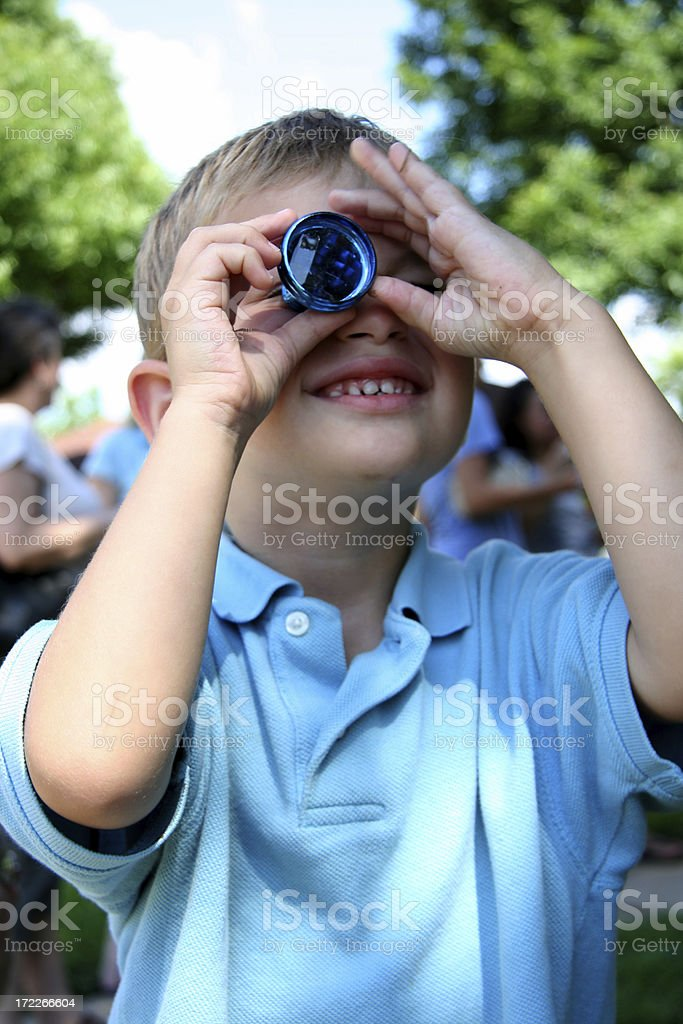Young Boy Looking Through A Toy Kaleidescope stock photo