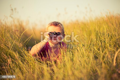 A young boy is looking through binoculars while hiding in the tall grass of an English field. He could be spying on or searching for something newsworthy. Image taken in the sunset light and with shallow depth of field.