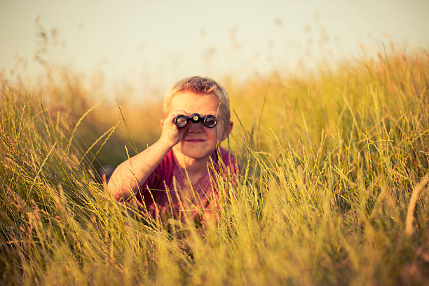 young boy looking through binoculars hiding in grass - searching stock photos and pictures