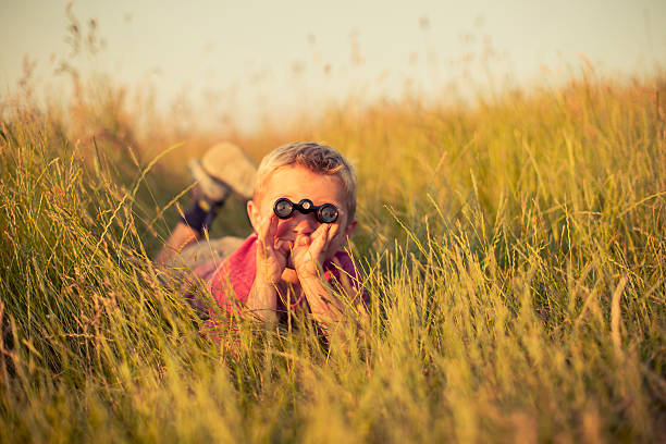 young boy looking through binoculars hiding in grass - binocular boy bildbanksfoton och bilder