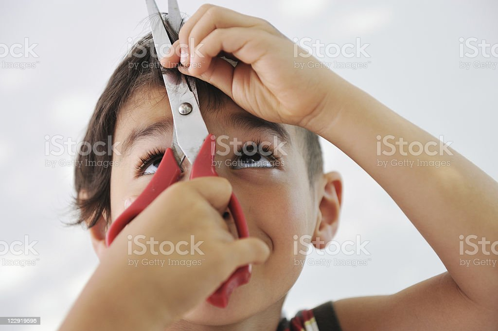 Young boy looking up at scissors while cutting own hair stock photo