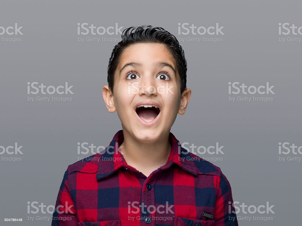 Young boy looking up with a shock expression stock photo